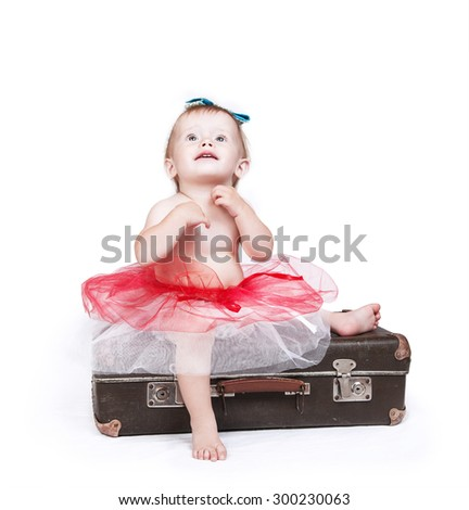 Little girl in tutu skirt sitting on the retro suitcase - stock photo