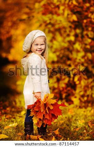 little girl in warm cardigan smiling against the background of fallen leaves - stock photo