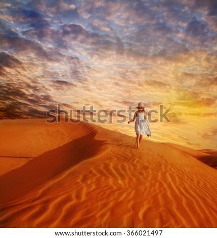 Little girl in white dress and hat walking down the sand dune in desert, at sunset - stock photo