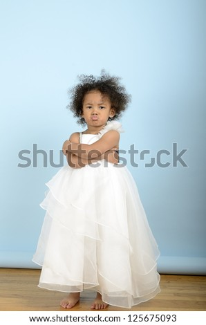 Little girl in white dress is not at all happy - stock photo