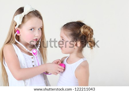 Little girl in white dress listens heartbeat of another girl by toy phonendoscope and looks at camera. Focus on left girl. - stock photo
