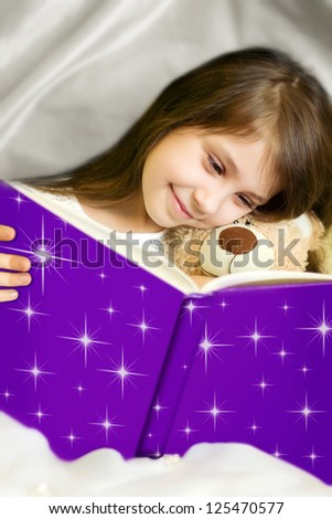 Little girl in white dress reading book with her toy bear - stock photo