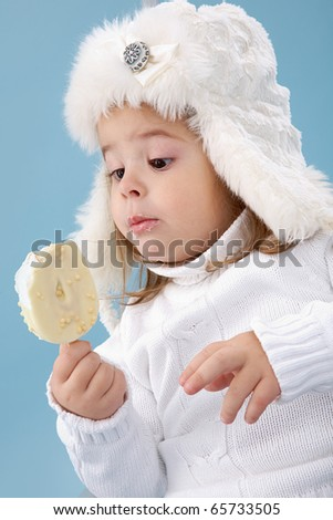 Little girl in white furry hat looking at ice-cream in her hands - stock photo