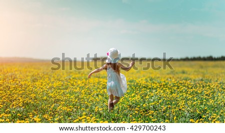 Little girl in white hat and white dress in a field of flowers in the summer. - stock photo