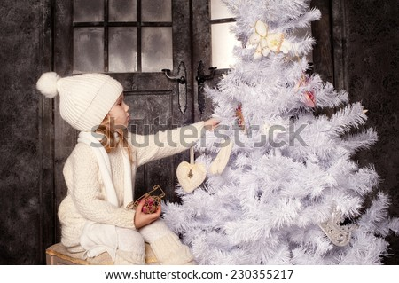 Little girl in white knitted clothes celebrating christmas and holding box with gift and surprise - stock photo