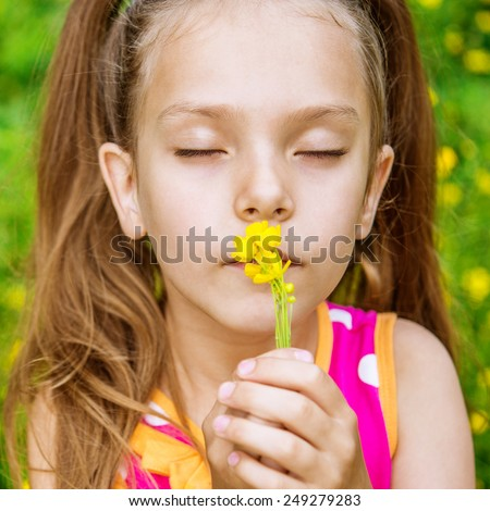 Little girl in yellow dress smells chamomile on green meadow. - stock photo