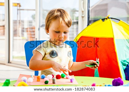 Little girl indoors painting and gluing - stock photo