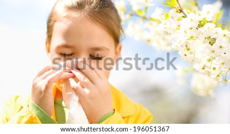 Little girl is blowing her nose near spring tree in bloom - stock photo
