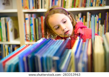 Little girl is choosing a book in the library. A child is looking at the books in the library deciding which one to take home. Children creativity and imagination. - stock photo