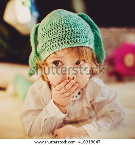 little girl is covering the mouth and hand - stock photo