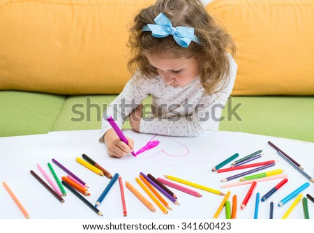 Little girl is drawing heart by colorful pencils. - stock photo