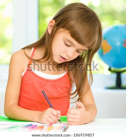 Little girl is drawing using color pencils while sitting at table - stock photo