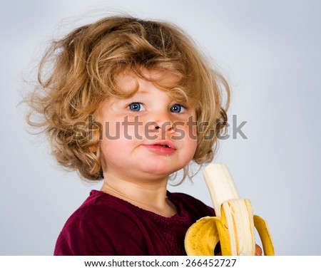 little girl is eating banana and looking in to the camera - stock photo