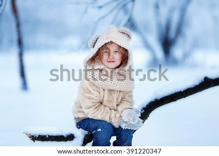 Little girl is enjoying a day out in the snow forest - stock photo