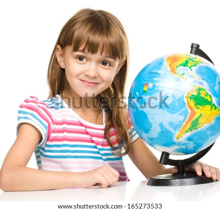 Little girl is examining globe while sitting at table, isolated over white - stock photo
