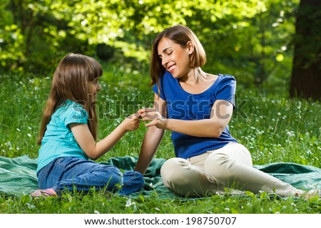 Little girl is giving flower to her mother while they sitting and enjoy in nature,Flower for you  - stock photo