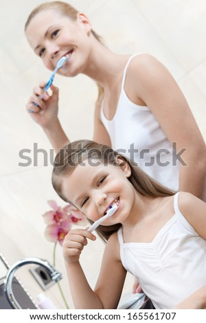 Little girl is happy to clean her teeth with her mom - stock photo