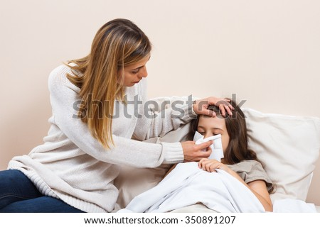 Little girl is having flu and mother is taking care of her.Little girl having flu  - stock photo
