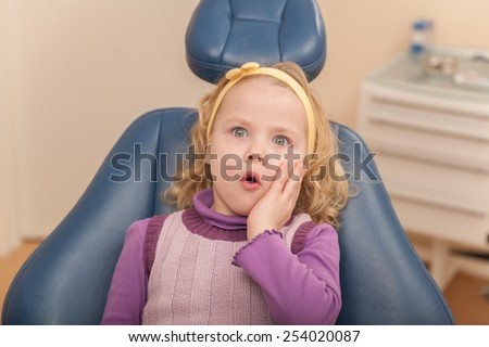 Little girl is having her teeth checked by dentist. frightened girl at dentist's office  - stock photo
