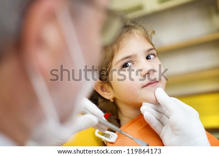 Little girl is having her teeth examined by dentist - stock photo