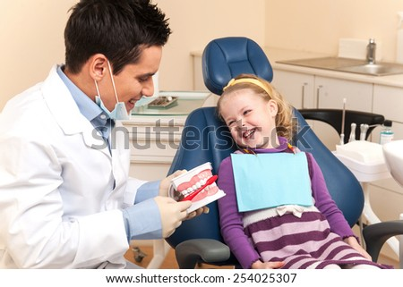 Little girl is having her teeth examined by dentist. dentist showing artificial teeth and brush to smiling girl in chair - stock photo