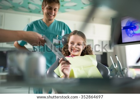 Little girl is having her teeth examined by dentist.Little girl sitting and smiling in the dentists office.Child not afraid of dentist.Dentist gives the patient a toothbrush and toothpaste.Dental care - stock photo
