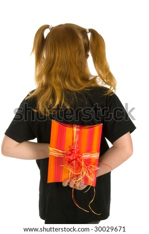 Little girl is hiding a present behind her back - stock photo