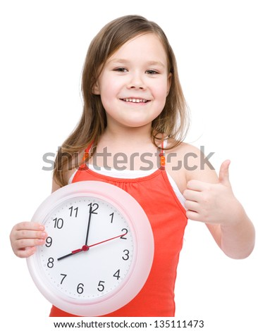 Little girl is holding big clock and showing thumb up gesture, isolated over white - stock photo