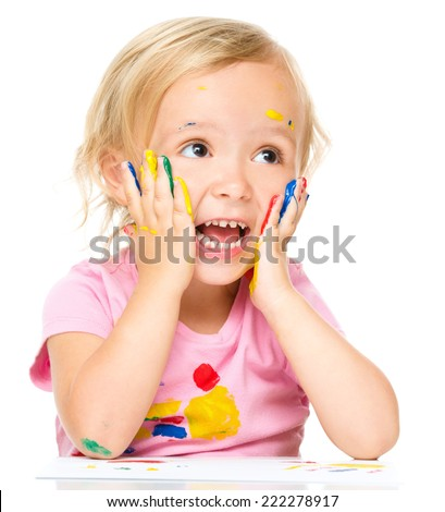 Little girl is holding her face in astonishment while playing with paints, isolated over white - stock photo