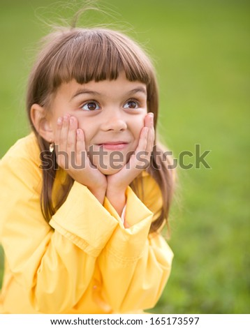 Little girl is holding her face while listening to somebody - stock photo