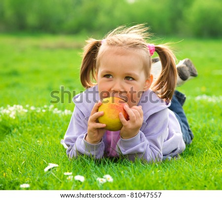 Little girl is laying on green meadow and going to eat a red apple - stock photo