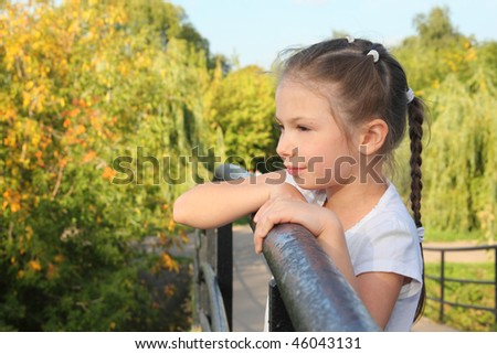 little girl is lean elbow on bridge fence and looking forward - stock photo