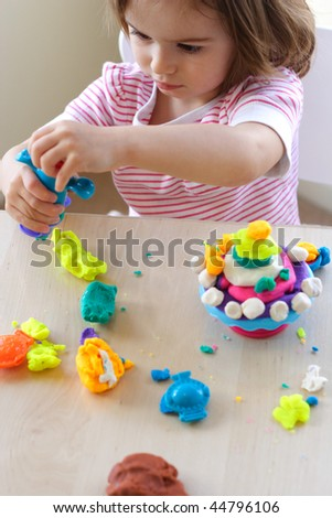Little girl is learning to use colorful play dough - stock photo