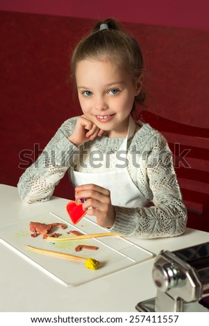 Little girl is learning to use colorful play dough in a well lit room  - stock photo