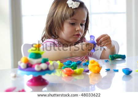 Little girl is learning to use colorful play dough in a well lit room near window - stock photo