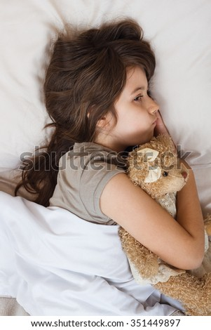 Little girl is lying on bed and she is very sad because of something.Sad little girl  - stock photo