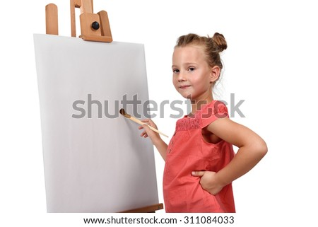little girl is painting on easel - stock photo
