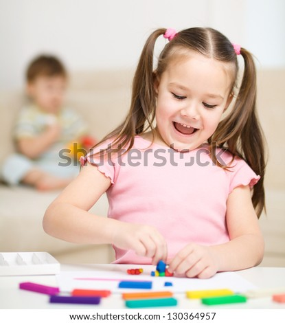 Little girl is playing with plasticine, her brother at the background - stock photo