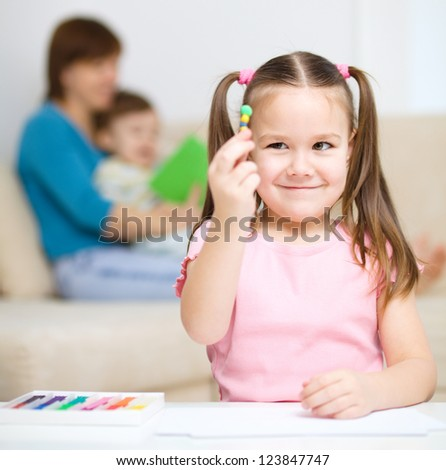 Little girl is playing with plasticine, her mother and brother at the background - stock photo