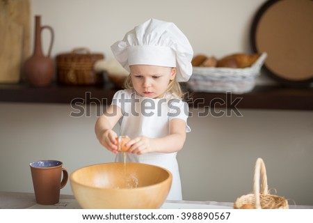 little girl is preparing a cake in a suit chef - stock photo