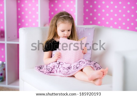 Little girl is reading a story while laying in bed and wearing pink dress, indoor shoot - stock photo