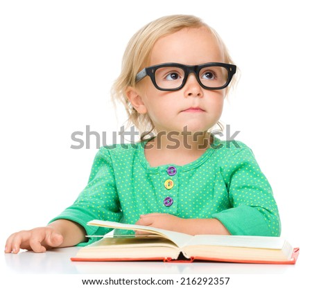 Little girl is reading her book while wearing glasses, isolated over white - stock photo