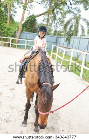 little girl is riding a horse - stock photo