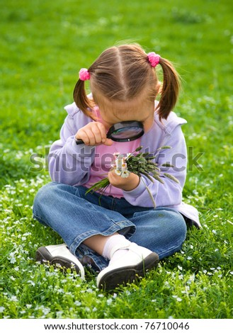Little girl is sitting on green meadow looking at herbs using magnifier - stock photo