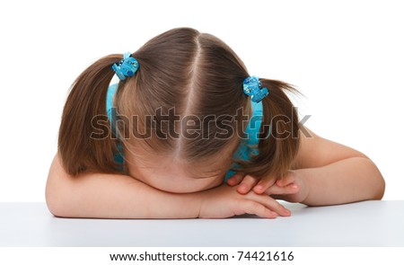 Little girl is sleeping at table laying her head on hands, isolated over white - stock photo