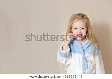 Little girl is standing with comb in her hand smiling wearing white bathrobe, Hygiene concept - stock photo
