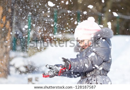 Little girl is throwing snow playing outdoors - stock photo