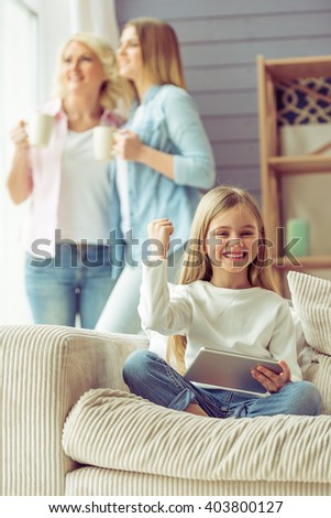 Little girl is using a tablet while sitting on sofa at home, in the background her mom and granny are looking out the window - stock photo