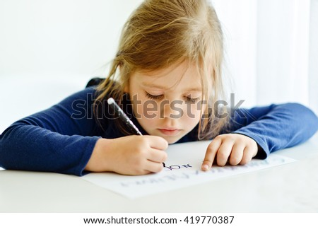 little girl is writing at the table - stock photo
