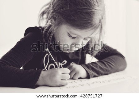 little girl is writting at the table - stock photo